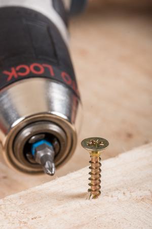 Metal screw screwed into a wooden board.