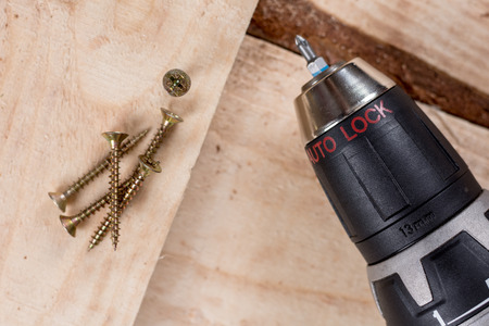 Metal screw screwed into a wooden board with accu drill. Stock Photo