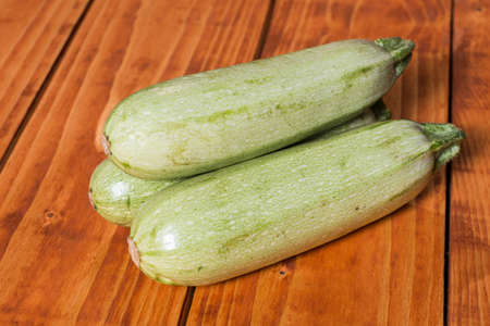 Whole raw zucchini on the wooden mahogany board planks.