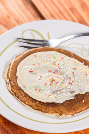 American pancakes topped with chocolate cream and colorful sprinkles. Stock Photo