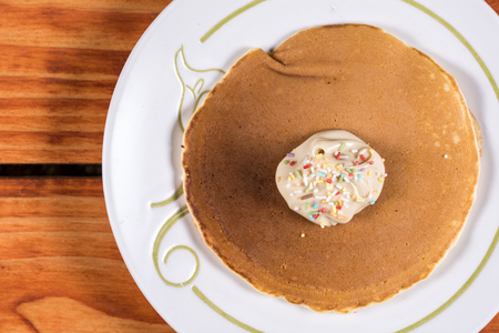 Chocolate cream with colorful sprinkles on the american pancakes.