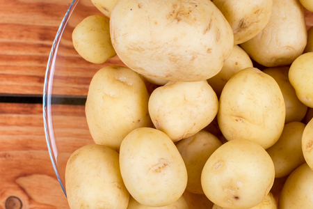 white washed: Young raw potatoes in the glass bowl above wooden background.