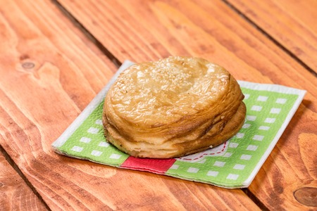 puff: Round puff pastry with sesame on the napkin over wooden background.