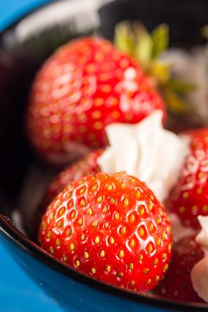 textured wall: Closeup macro fresh strawberries in whipped cream. Stock Photo