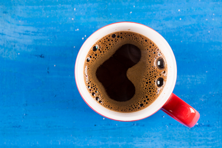 heart shaped: Flat lay cup of coffee with heart shape above blue wooden background.