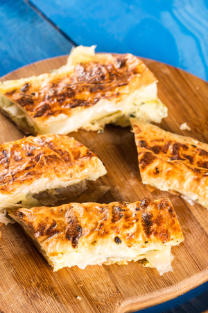 Slices of baked cheese pie served on the retro rustic round wooden board.