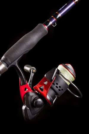 Fishing reel on the stick with black background. Stock Photo