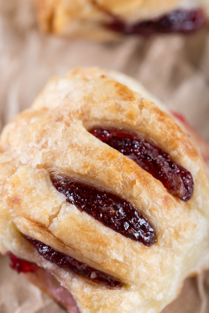Domestic buns with strawberry jam on the wrinkled brown paper. Stock Photo