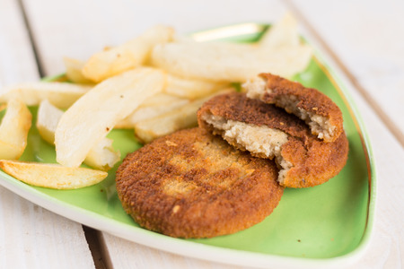 plate: Fried fish meat burgers served with french fries on the plate.