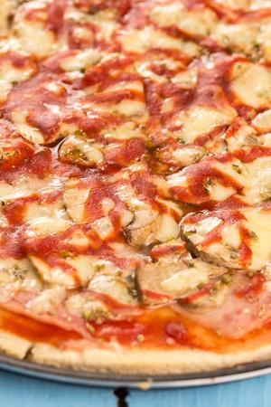 junk: Closeup macro fresh baked round pizza with cheese ham tomato sauce mushrooms. Stock Photo