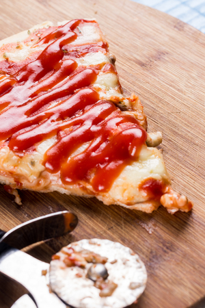 junk: Flat lay above fresh baked pizza triangle slice on the wooden board with cutting knife.