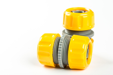 Yellow plastic water hose connectors over white background with copy space.