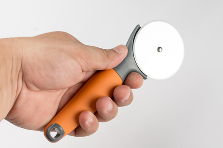 pizza cutter: Black and orange round pizza knife in the hand isolated over white background with copy space.