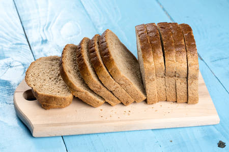 whole wheat toast: Sliced healthy dark bread on the wooden kitchen board. Stock Photo