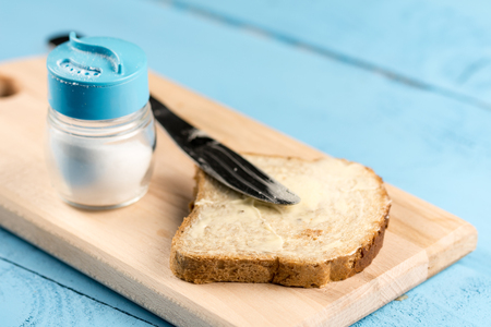 Flat lay butter spread on bread with knife and saltshaker served on a wooden board.