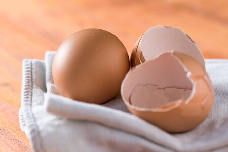 Egg and eggshells on the kitchen dishtowel with natural moody backlight. Standard-Bild