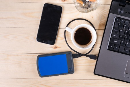 Flat lay above lap top computer on the wooden table with external hard disc hdd mobile phone cup of coffee and ashtray and with copy space. Stock Photo