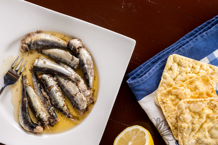 Marinated sardines in the oil served with lemon and corn bread.