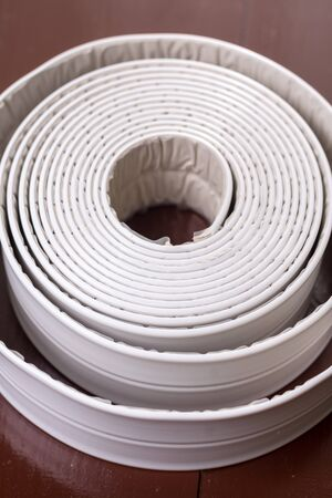 gasket: White sanitary sealant strip on the wooden brown table.