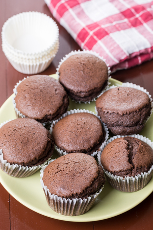 Fresh baked chocolate cup cakes served on the plate with kitchen dishtowel in the background.
