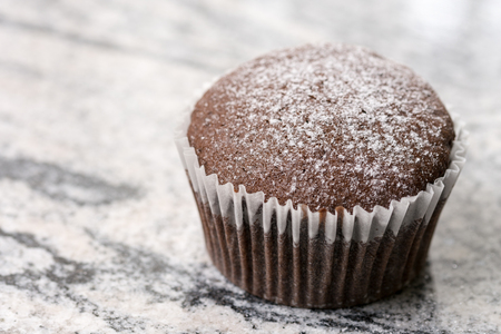 textured wall: Chocolate cup cake with powdered sugar on the grey granite background. Stock Photo