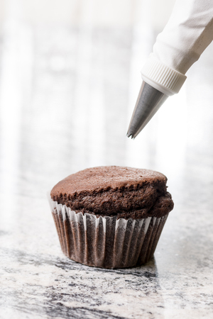 chantilly: Piping bag with chocolate ganache cream above chocolate cup cake on the grey granite background.