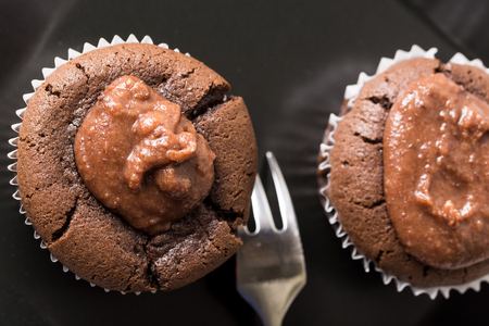black textured background: Flat lay above chocolate cup cake muffin on the black square plate. Stock Photo