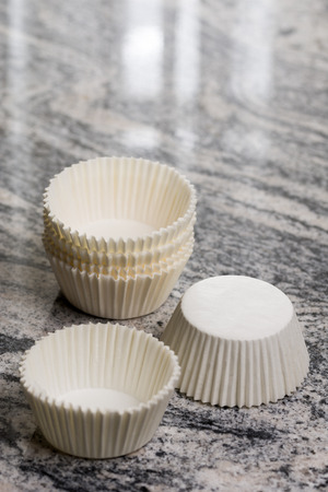 food supply: Empty white cup cake cases containers on the grey granite marble background. Stock Photo