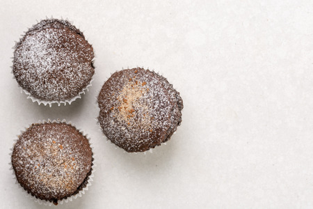 Flat lay above chocolate brownies cup cakes with powdered sugar on the white marble background. Stock Photo