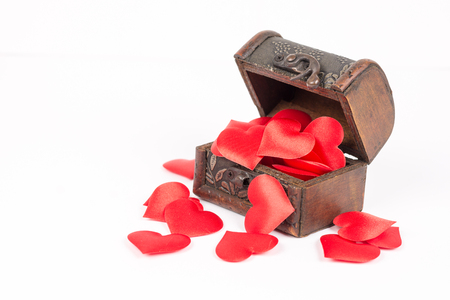 Antique rustic brown wooden coffin isolated above white background and filled with romantic red hearts of love. Stock Photo