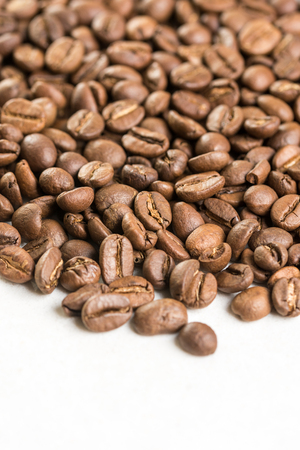 Pile of coffee beans with copy space above white marble stone. Stock Photo