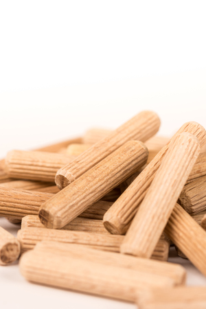 Pile of wooden dowels isolated on white background. Stock Photo