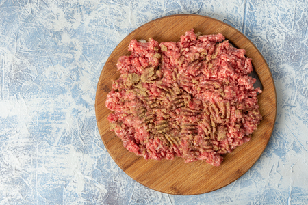 Minced meat mixture on the kitchen wooden board above blue background.