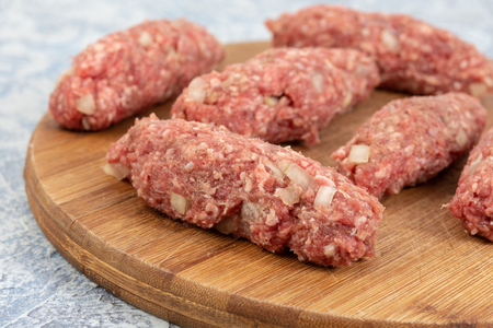 Prepared Raw Minced Meat Kebabs On The Kitchen Wooden Board.
