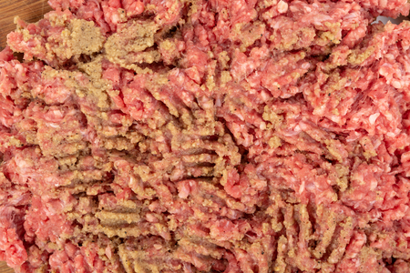 Minced meat mixture on the wooden board for kebabs.