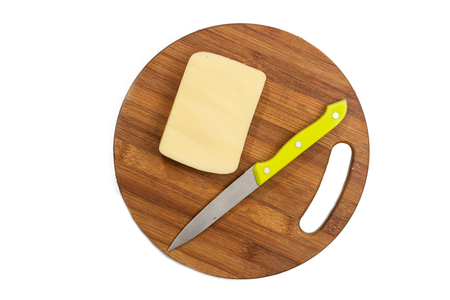 Piece of yellow cheese on the cutting board with knife