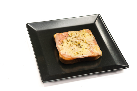 Toasted sandwiches with grated yellow cheese and ham on the plate