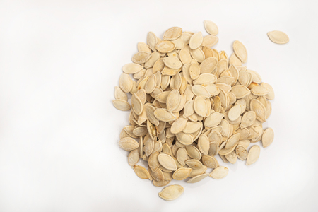 Dried pumpkin seeds isolated above white background.
