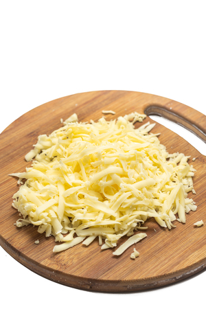 Grated yellow cheese on the wooden cutting board. Stok Fotoğraf