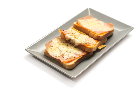 Toasted sandwiches with grated yellow cheese and ham on the plate.