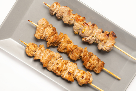 Fried pork meat kebabs on the wooden stick served on the plate.