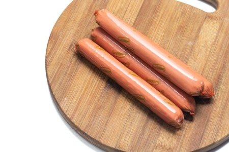 Raw hot dogs on the cutting wooden board.