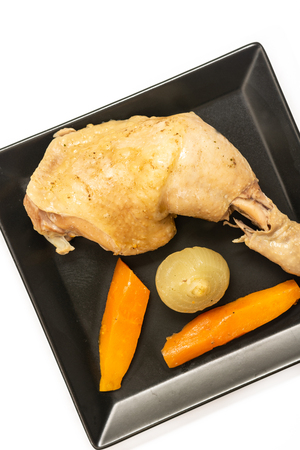 Cooked chicken drumstick with carrot on the plate.