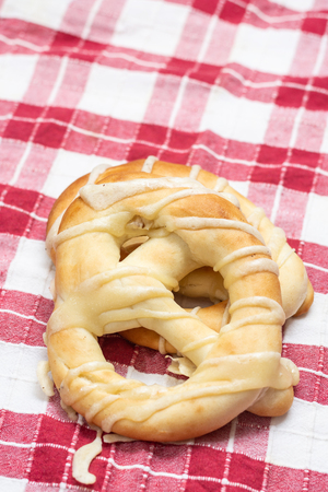 Fresh bakery pretzels isolated above white background on the wooden board.