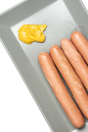 Cooked hot dogs on the plate with mustard.