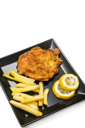 Fried pork meat steak with lemon on the plate.