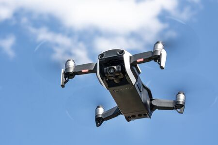 Flying drone with recording camera with blue sky behind.