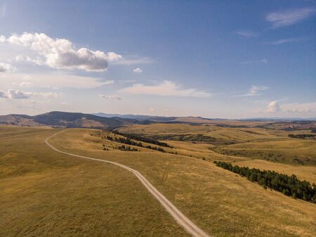 Aerial image of Zlatibor mountain in Serbia. Beautiful landscape image with yellow fields and blue sky Reklamní fotografie - 128830607