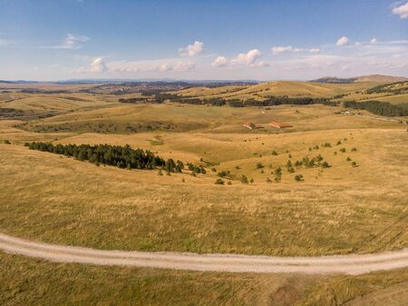 Aerial image of Zlatibor mountain in Serbia. Beautiful landscape image with yellow fields and blue sky Reklamní fotografie - 128830619