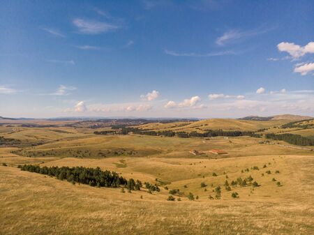 Aerial image of Zlatibor mountain in Serbia. Beautiful landscape image with yellow fields and blue sky Reklamní fotografie - 128830623